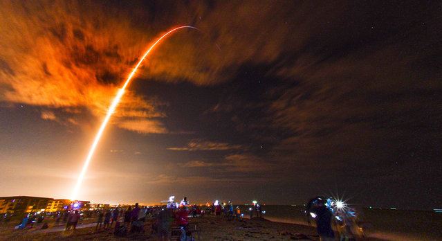 Crowds on the beach in Cape Canaveral, Fla., watch the launch of the SpaceX Falcon 9 Crew Dragon on its Crew-1 mission carrying four astronauts, Sunday, November 15, 2020, in this 3 1/2-minute time exposure. The rocket was launched from Launch Complex 39A at Kennedy Space Center at 7:27 p.m. Sunday evening. (Photo by Malcolm Denemark/Florida Today via AP Photo)