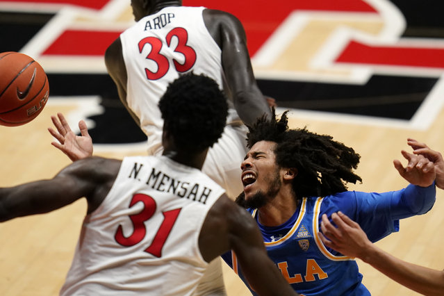 UCLA guard Tyger Campbell, right, loses control of the ball as San Diego State forward Nathan Mensah (31) defends during the first half of an NCAA college basketball game Wednesday, November 25, 2020, in San Diego. (Photo by Gregory Bull/AP Photo)