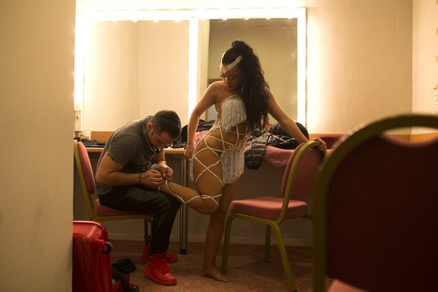 In this Friday, November 6, 2015 photo dancers Alba Ibanez, right, and Luis Chavez, both from Spain, dress up backstage before taking part in the World Salsa Master dance competition in Madrid. (Photo by Francisco Seco/AP Photo)