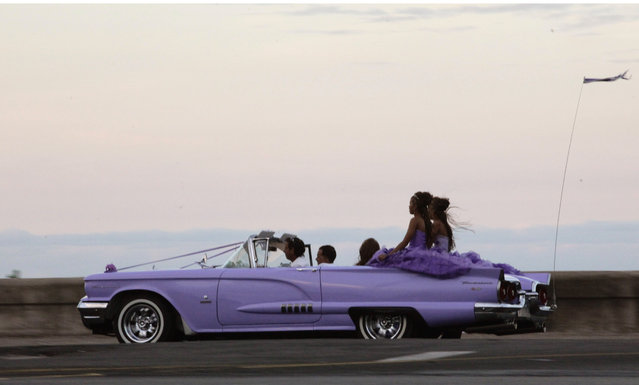 In this December 19, 2014 photo, girls ride on the back of an American vintage car along the Malecon during a 15th birthday celebration in Havana, Cuba. (Photo by Desmond Boylan/AP Photo)