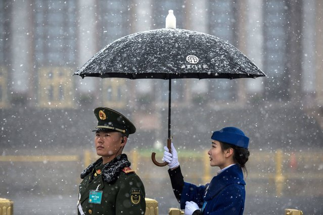 A hostess holds an umbrella for a paramilitary police for a picture at the Great Hall of the People, where China's President Xi Jinping was elected for a second term during the fifth plenary session of the first session of the 13th National People's Congress (NPC), in Beijing on March 17, 2018. China's rubber-stamp parliament unanimously handed President Xi Jinping a second term on March 17 and elevated his right-hand man to the vice presidency, giving him a strong ally to consolidate power and handle US trade threats. (Photo by Fred Dufour/AFP Photo)