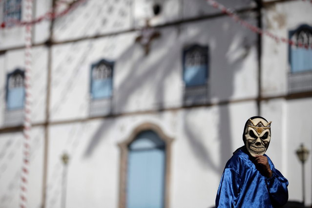 """A masked boy walks past Our Lady of the Rosary church, during the """"Cavalhadas"""" festival, in Pirenopolis, Brazil, Sunday, May 19, 2013. The popular festival is a tradition that was introduced in the 1800's by a Portuguese priest to mark the the ascension of Christ. The 3-day festival reenacts the Christian knights' defeat of the Moors. (Photo by Eraldo Peres/AP Photo)"""