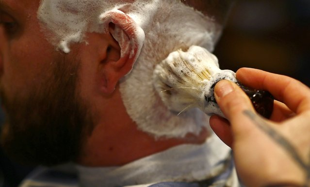 "Alex ""Torreto"" Vellios, a 26-year old Greek-born barber applies lather a customer for a shave at his Torreto barber shop in Frankfurt January 6, 2015. (Photo by Kai Pfaffenbach/Reuters)"