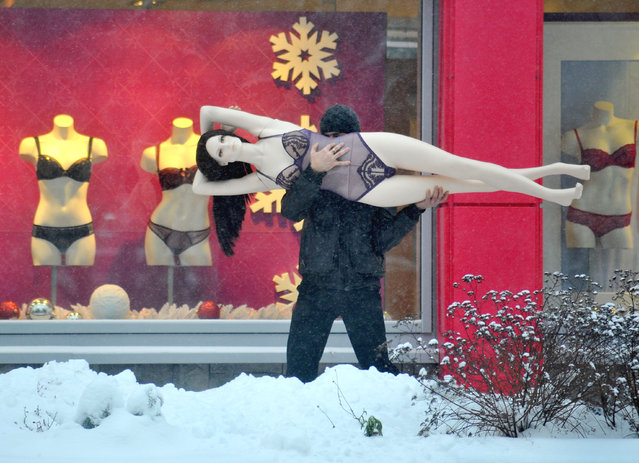 A man carries a mannequin in the Belarus capital Minsk, on December 10, 2012. (Photo by Viktor Drachev/AFP Photo)
