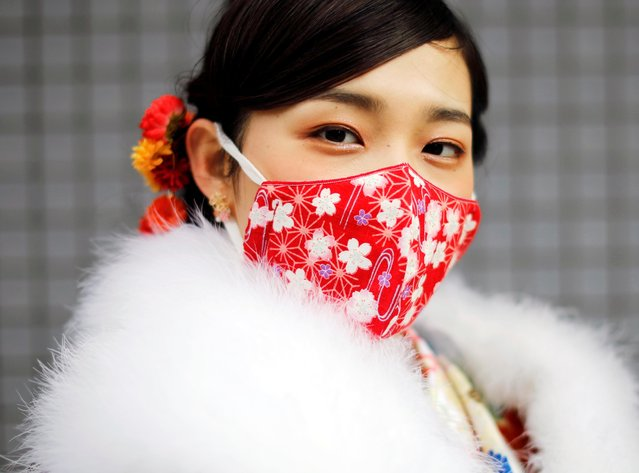 A Kimono-clad woman wearing a fashionable face mask poses for a photograph at Coming of Age Day celebration ceremony at Yokohama Arena after the government declared the second state of emergency for the capital and some prefectures, amid the coronavirus disease (COVID-19) outbreak, in Yokohama, south of Tokyo, Japan on January 11, 2021. Young men and women in masks braved cold weather in lines and sat seats apart from one another in Yokohama to mark Japan's Coming of Age Day, even though the city is under a state of emergency. (Photo by Issei Kato/Reuters)