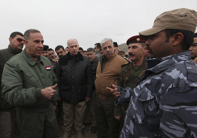 Iraqi Defence Minister Khaled al-Obeidi (L) speaks to members of Iraqi security forces during training, as they prepare to fight against militants of the Islamic State, at a training camp on the outskirts of Mosul January 10, 2015. (Photo by Azad Lashkari/Reuters)