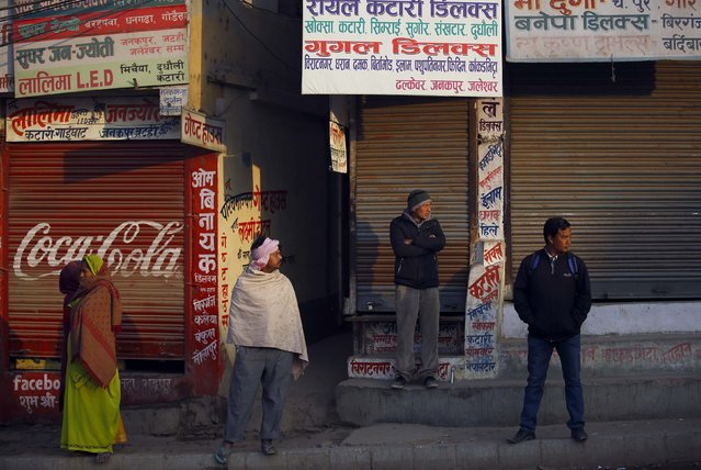 Nepalese stand in front of a closed shops as they look towards protesters (unseen) during the general strike independently called by the Unified Communist Party of Nepal (Maoist) and led by 30 party alliance and the Communist Party of Nepal (Maoist), demanding that the drafting of the new constitution is done on time through consensus, in Kathmandu January 13, 2015. (Photo by Navesh Chitrakar/Reuters)
