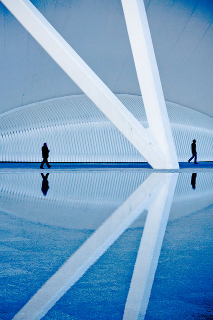 """Seeing Double"". Two figures walk along one of the reflecting pools at Santiago Calatrava's futuristic architectural wonder – The City of Arts and Sciences, in Valencia, Spain – a massive space full of lines, repetitions & reflections. Location: City of Arts & Sciences, Valencia, Spain. (Photo and caption by Erika Szostak/National Geographic Traveler Photo Contest)"