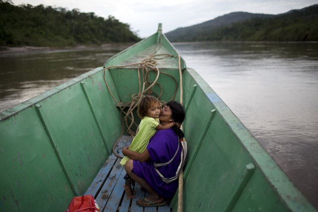 "In this November 20, 2015 photo, Ashaninka indigenous woman Nancy Cherencente and her daughter Leila sit in an embrace as they travel by boat from Potsoteni to Pichiquia, in Peru's Junin region. Caleb Cabello, a teacher in Potsoteni where there's a free meal program at public schools, said he says goodbye to students at his boarding school at the end of November, watching them leave by boat to their distant settlements. ""They go home a little fat and the return very thin"", he said. (Photo by Rodrigo Abd/AP Photo)"