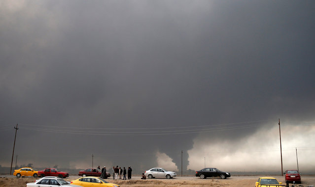 Men stand on a road in Qayyara as smoke rises from oilfields burned by Islamic State fighters, south of Mosul, Iraq November 10, 2016. (Photo by Goran Tomasevic/Reuters)