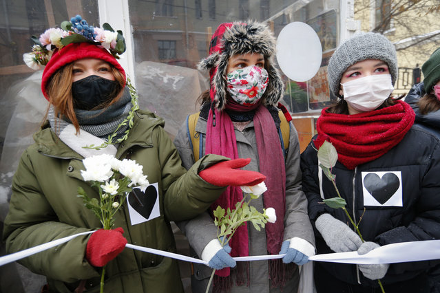 Women, wearing face masks to protect against coronavirus, attend a rally in support of jailed opposition leader Alexei Navalny and his wife Yulia Navalnaya, in Moscow, Russia, Sunday, February 14, 2021. (Photo by Alexander Zemlianichenko/AP Photo)