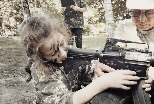 A girl trains with a weapon at a paramilitary youth camp. (Photo by Aude Osnowycz/Hans Lucas/The Guardian)