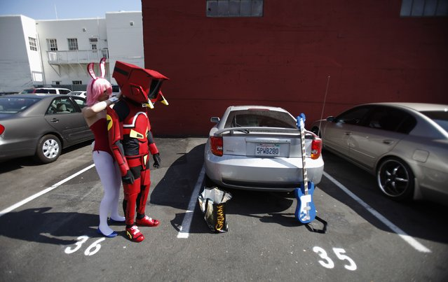 """Attendees Emil Buenafe and Marisa Meyer finish up getting ready in their costumes of """"Canti"""" and """"Haruko"""" from the animated series """"FLCL"""" during the Comic Con International convention in San Diego, California July 13, 2012. (Photo by Mario Anzuoni/Reuters)"""