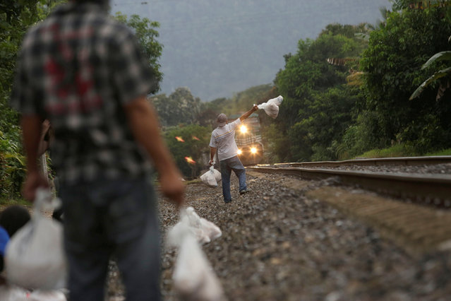 "Volunteers from a group called ""Las Patronas"" (The bosses), a charitable organization that feeds Central American immigrants who travel atop a freight train known as ""La Bestia"", hold bags with food and water for immigrants on their way to the border with the United States, at Amatlan de los Reyes, in Veracruz state, Mexico October 21, 2016. (Photo by Daniel Becerril/Reuters)"