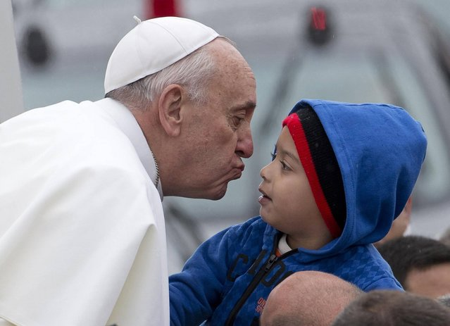 Pope Francis reaches out to kiss a child as he arrives to the Aparecida Basilicia in Aparecida, Brazil, Wednesday, July 24, 2013. (Photo by Domenico Stinellis/AP Photo)
