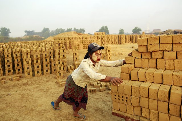 A woman works at a brick kiln on the outskirts of Yangon February 1, 2015. (Photo by Soe Zeya Tun/Reuters)