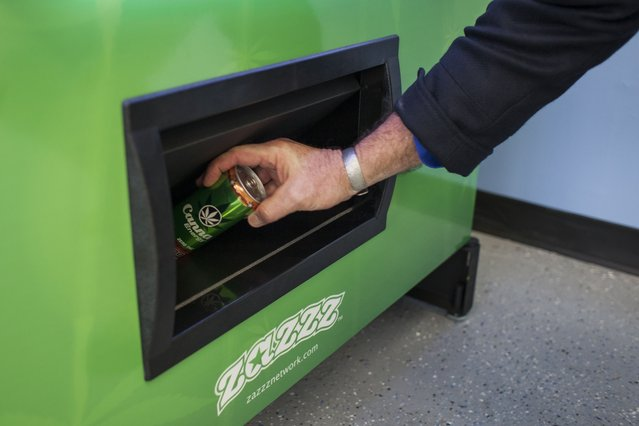 Stephen Shearin retrieves a can of Canna Energy Mango as he demonstrates the use of a ZaZZZ vending machine that contains cannabis flower, hemp-oil energy drinks, and other merchandise at Seattle Caregivers, a medical marijuana dispensary, in Seattle, Washington February 3, 2015. (Photo by David Ryder/Reuters)
