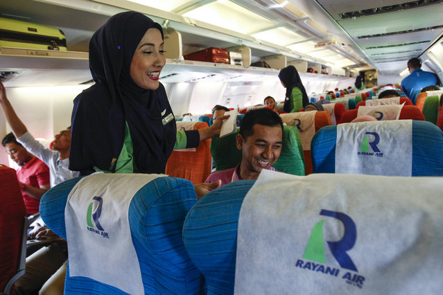 In this December 22, 2015, photo, a Rayani Air flight crew, left, shares a light moment with passengers on board at Kuala Lumpur International Airport 2 in Sepang, Malaysia. Malaysia's Rayani Air took to the skies over the weekend with a clear bailiwick. It is the country's first Islamic airline, offering flights that adhere to Islamic rules including prayers, no-alcohol, no-pork meals, and a strict dress code for Muslim female flight attendants. (Photo by Joshua Paul/AP Photo)
