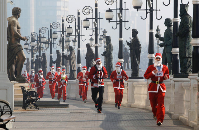 People costumed as Santa Claus run through a statue alley during a Santa Claus Race in Macedonia's capital Skopje, Sunday, December 27, 2015. A few hundred people dressed as Santa Claus participated in a race ahead of New Year through the streets of Skopje. (Photo by Boris Grdanoski/AP Photo)