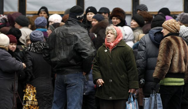 Residents gather as the humanitarian aid is distributed to residents in the town of Debaltseve, Ukraine, Friday, February 6, 2015. (Photo by Petr David Josek/AP Photo)