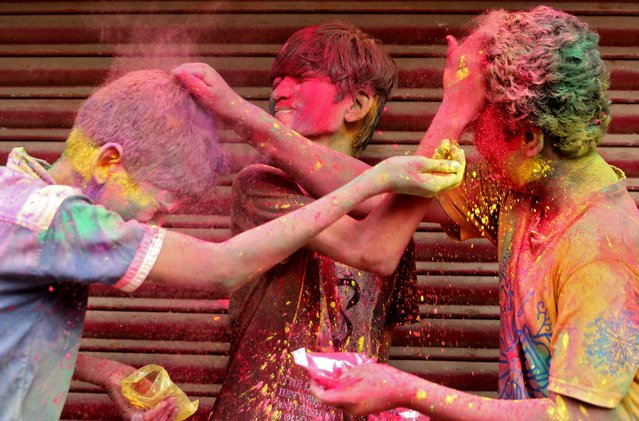 Boys apply colour powder on each other during Holi celebrations, amidst the spread of the coronavirus disease (COVID-19), in Chennai, India, March 29, 2021. (Photo by P. Ravikumar/Reuters)