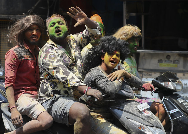 Youth, with their faces smeared with colored powder, ride on motor bikes during Holi festivities in Hyderabad, India, Monday, March 29, 2021. (Photo by Mahesh Kumar A.)/AP Photo