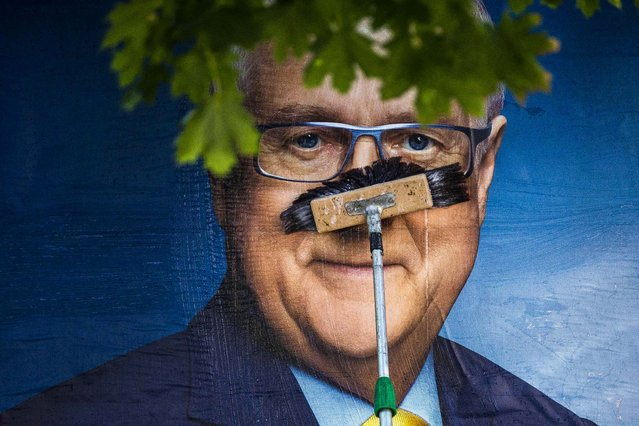 A worker pastes up an election poster showing Rainer Bruederle, the top candidate of the liberal Free Democratic Party in the upcoming German general elections, in Berlin, on August 26, 2013. Voters will take to the polls on September 22. (Photo by Thomas Peter/Reuters)