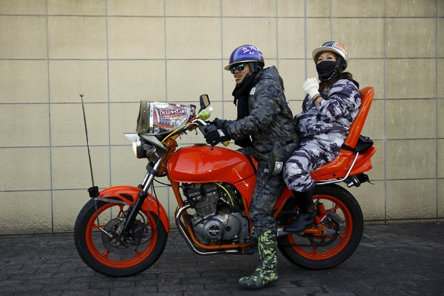 A man and a woman pose on a Bousouzoku motorbike at the Dangouzaka rest stop in Yamanashi, west of Tokyo, Japan, January 3, 2016. (Photo by Thomas Peter/Reuters)