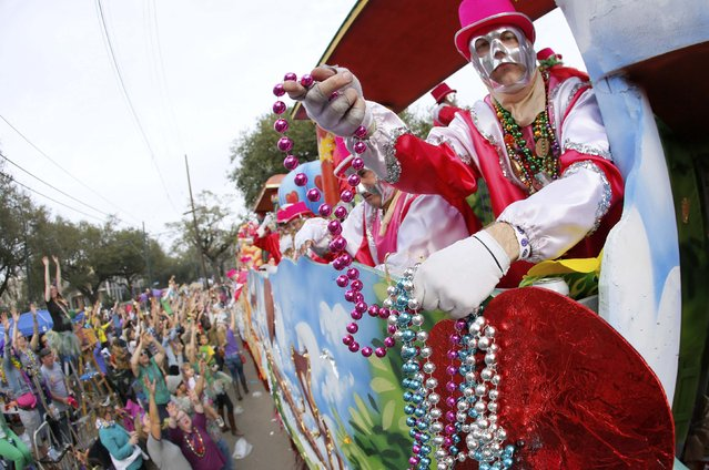 A member of the Krewe of Thoth throws beads during a Mardi Gras parade in New Orleans, Louisiana February 15, 2015. (Photo by Jonathan Bachman/Reuters)