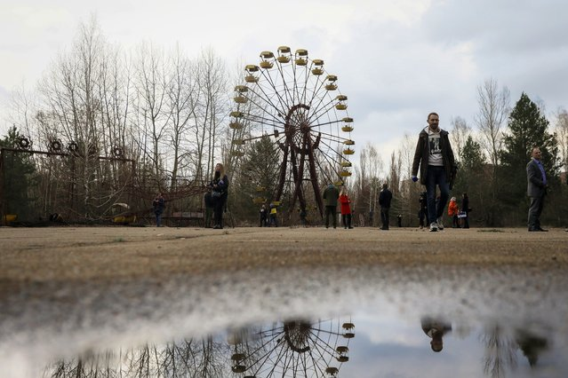 People walk near the ferris wheel in abandoned city of Prypyat, near Chernobyl, Ukraine, 15 April 2021. Ukraine will mark the 35th anniversary of Chernobyl tragedy on 26 April 2021. The explosion of reactor 4 of the Chernobyl nuclear power plant in the early hours of 26 April 1986 is still regarded as the worst nuclear disaster ever. (Photo by Oleg Petrasyuk/EPA/EFE)