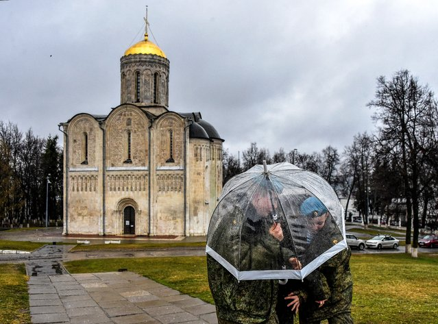 Cadets hide from the rain under an umbrella near a church in the town of Vladimir on April 21, 2021, where jailed Kremlin critic Alexei Navalny was reportedly transferred to the IK-3 penal colony. Russia's ties with the West have deteriorated to Cold War levels, with Moscow and Western capitals at loggerheads over jailed Kremlin critic Alexei Navalny, a Russian troop build-up on Ukraine's borders and a series of espionage scandals. (Photo by Vasily Maximov/AFP Photo)