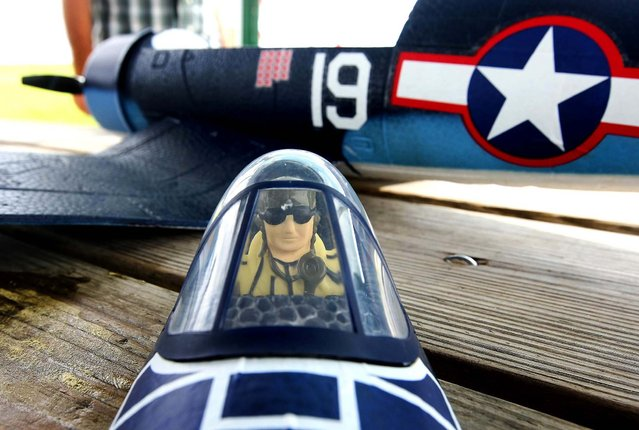 A WWII pilot rests in the removable cockpit of a remote control plane at Phil Wherry Field. (Photo by Bill Ingram/The Palm Beach Post)