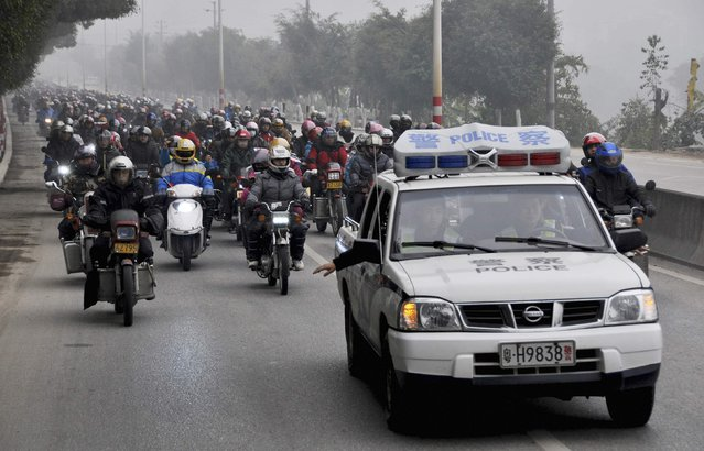 A police car leads along a street as migrant workers ride their motorcycles to go home for the upcoming Spring Festival, on a hazy day in Fengkai county, Guangdong province, February 12, 2015. (Photo by Reuters/China Daily)