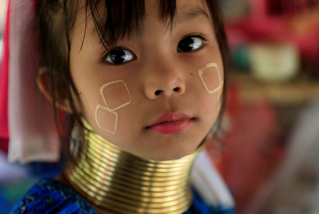 An Ethnic Kayan also know as a Long Neck girl sits at her parents souvenir shop in the Kayan village at the northern province of Chiang Rai, Thailand, July 16, 2018. (Photo by Soe Zeya Tun/Reuters)