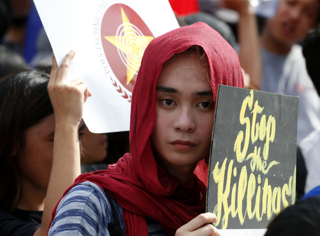 """Students display placards during a rally near the Presidential Palace to protest alleged military's """"red-tagging"""" of Metro Manila schools and universities and linking them to an alleged plot to topple President Rodrigo Duterte known as """"Red October"""" Friday, October 12, 2018 in Manila, Philippines. The students assailed the military for releasing the list of schools allegedly being used by the communist movement to recruit its members only to admit later that their information still has to be verified. (Photo by Bullit Marquez/AP Photo)"""