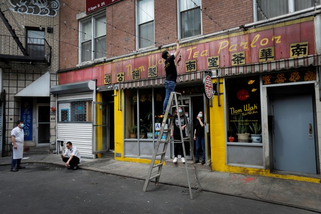 Workers at the Nom Wah Tea Parlor dim sum restaurant, open since 1920, hang lights outside as they open for business for the day on Doyers Street nearby the site of the May 31, 2021 unprovoked attack on an Asian person, a 55 year old woman, in Manhattan's Chinatown district in New York City, U.S. June 2, 2021. (Photo by Mike Segar/Reuters)