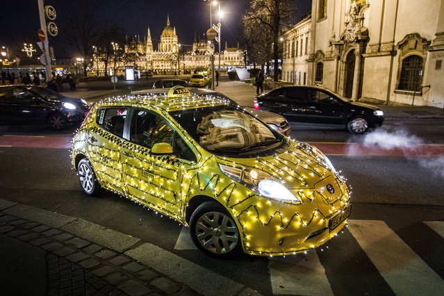 In this picture made available Tuesday, Dec. 6, 2016 shows a taxi decorated with Christmas lights cruising at Batthyany square in downtown Budapest, Hungary, Monday, December 5, 2016. The festive taxi, along with its daily duty, delivers donations to the Tuzolto Utca Children's Clinic. The donations are collected by the taxi firm. (Photo by Zsolt Szigetvary/MTI via AP Photo)