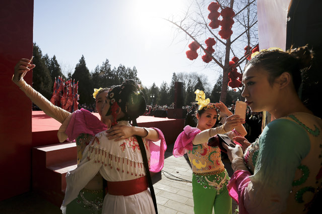 Chinese dancers dressed in traditional costume take selfies in backstage during a temple fair for a Lunar New Year celebration in Beijing, Monday, February 8, 2016. (Photo by Andy Wong/AP Photo)