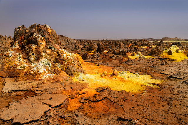 Thanks to plenty of salt minerals and heavy elements in the soil, the Dallol volcano in Ethiopia produces brilliantly colored pools of water at the top of its caldera. And, as if to add greater effect to the already stunning sights, the volcano stands apart from the salt plains around it like an island. This hotspot was created through phreatomagmatic eruptions caused by magma interacting with water, and was further altered due to the presence of salt water. (Photo by Francisco Pandolfo/Caters News)