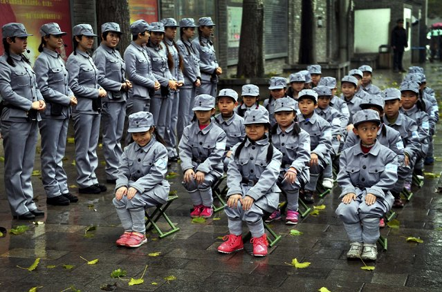 Primary school students wearing army uniforms sit next to museum guides as they are organized to experience the life of the Eighth Route Army soldiers inside a yard of a Chinese revolutionary museum in Xi'an, on November 23, 2013. (Photo by China Daily)