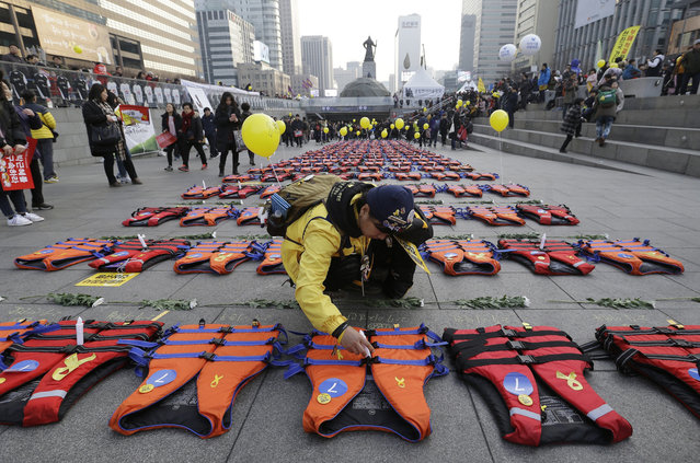 """An unidentified mother of the 304 victims of sunken ferry Sewol in 2014 places a light stick on a life vest symbolizing them before a candle light vigil calling for impeached President Park Geun-hye to step down in Seoul, South Korea, Saturday, January 7, 2017. Prosecuting lawmakers accused Park of """"broadly and gravely"""" violating the constitution as the Constitutional Court began hearing oral arguments Thursday in her impeachment trial. (Photo by Ahn Young-joon/AP Photo)"""