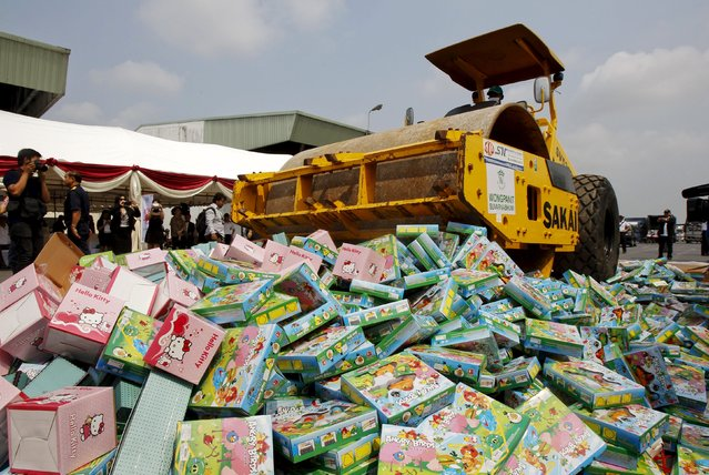 Thai Department of Intellectual Property and police officials destroy counterfeit goods at Khlongluang Transportation Station in Pathumtani province, on the outskirts of Bangkok April 9, 2015. (Photo by Chaiwat Subprasom/Reuters)