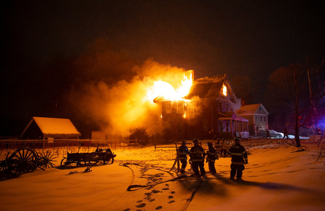 Fire fighters work on extinguishing a fire at an old farm house in Billerica, Massachusetts, USA, 21 January 2019. The temperature at the time was –17 degrees Celsius and near-by hydrants were not working causing a difficulty situation for fire fighters at the scene of the fire. (Photo by C.J. Gunther/EPA/EFE)