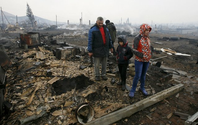 Local residents stand amidst the debris of a burnt building in the settlement of Shyra, damaged by recent wildfires, in Khakassia region, April 13, 2015. (Photo by Ilya Naymushin/Reuters)