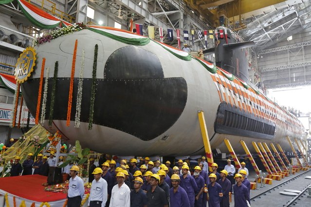 Employees stand in front of the Indian Navy's first Scorpene submarine before being undocked from Mazagon Docks Ltd, a naval vessel ship-building yard, in Mumbai April 6, 2015. (Photo by Shailesh Andrade/Reuters)