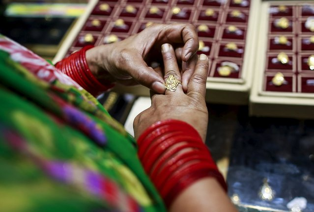 A woman tries a gold ring at a jewellery showroom in Mumbai in this October 21, 2014 file photo. India's overseas gold purchases are likely to hit a more than two-year low in February, as rising prices and hopes for a cut in import taxes keep buyers away, industry sources said. (Photo by Danish Siddiqui/Reuters)