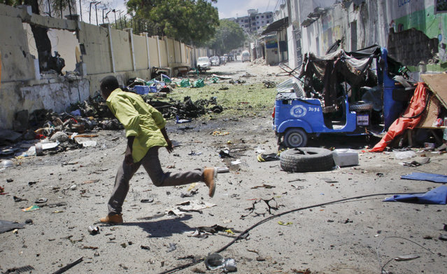 A man runs for cover during fighting following a car bomb that was detonated at the gates of a government office complex in the capital Mogadishu, Somalia Tuesday, April 14, 2015. (Photo by Farah Abdi Warsameh/AP Photo)