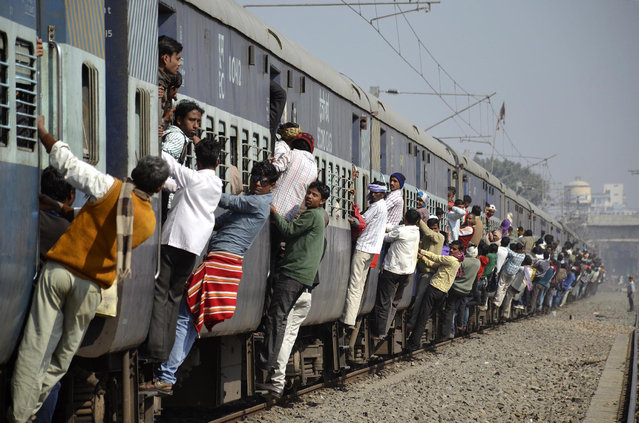 Commuters hang onto a crowded local passenger train in the eastern Indian city of Patna, February 12, 2014. (Photo by Krishna Murari Kishan/Reuters)