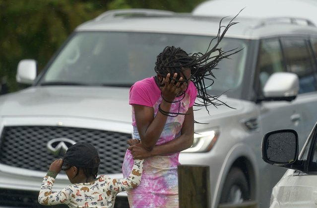A young girl blocks her face from the wind and rain produced by Hurricane Ida, Sunday, August 29, 2021, in New Orleans, La. (Photo by Eric Gay/AP Photo)