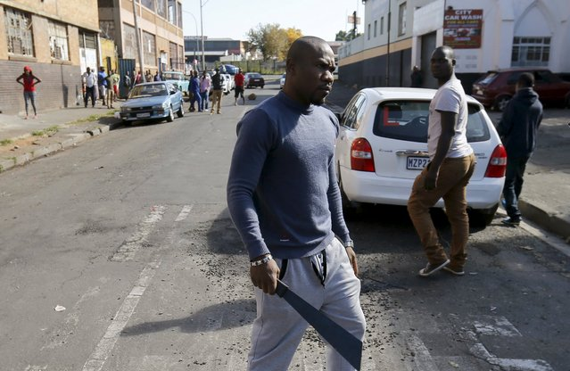 An African immigrant holds a machete before being dispersed by police officers in Johannesburg, April 17, 2015. (Photo by Siphiwe Sibeko/Reuters)